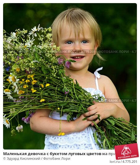 Маленькая девочка с букетом луговых цветов на природе; фотограф Эдуард