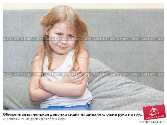 Обиженная маленькая девочка сидит на диване сложив руки на груди, фото.