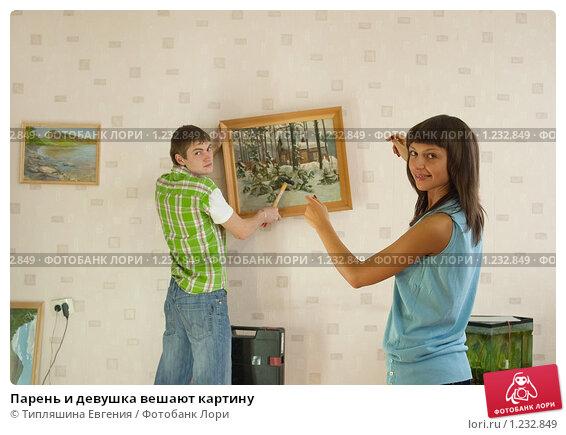 Парень и девушка вешают картину фото