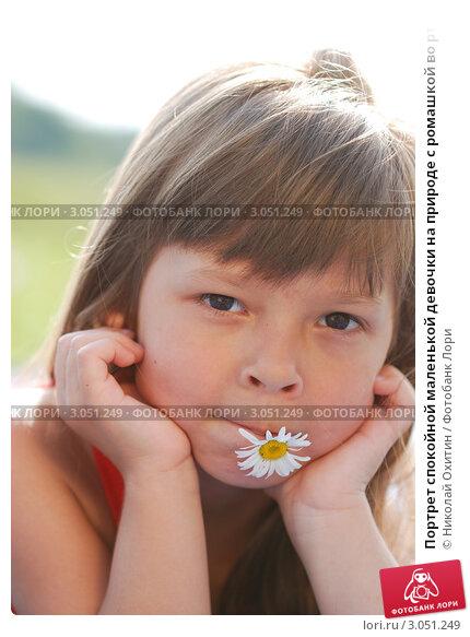 Портрет спокойной маленькой девочки на природе с ромашкой во рту