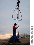 Рабочий поддерживает стропы на фоне вечернего неба (2007 год). Редакционное фото, фотограф Крупнов Денис / Фотобанк Лори