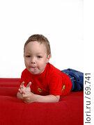 Купить «Маленький мальчик лежит на красном диване, с высунутым язычком», фото № 69741, снято 4 июня 2007 г. (c) Harry / Фотобанк Лори