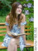 Девушка, сидящая на скамейке в окружении цветов и мечтающая над книгой. Стоковое фото, фотограф Влада Посадская / Фотобанк Лори