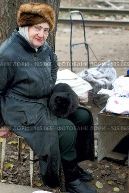 Купить «Пожилая женщина, продавец, на улице, с кошкой на коленях», фото № 105065, снято 19 сентября 2018 г. (c) Александр Чураков / Фотобанк Лори