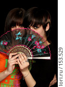 Купить «Две девушки держат веер в руках, на черном фоне», фото № 153529, снято 4 мая 2007 г. (c) Александр Паррус / Фотобанк Лори