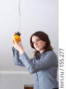 Купить «Девушка  вкручивает в патрон  апельсин вместо лампочки», фото № 155277, снято 5 декабря 2007 г. (c) Ирина Мойсеева / Фотобанк Лори