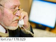Купить «Пожилой человек говорит по телефону на рабочем месте в офисе перед компьютером», фото № 178029, снято 16 января 2008 г. (c) Олег Селезнев / Фотобанк Лори
