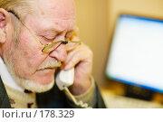 Купить «Пожилой человек говорит по телефону на рабочем месте в офисе перед компьютером», фото № 178329, снято 16 января 2008 г. (c) Олег Селезнев / Фотобанк Лори