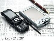 Мобильный телефон и КПК на фоне газеты. Стоковое фото, фотограф Андрей Зык / Фотобанк Лори