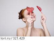 Купить «Девушка с леденцами в форме сердец на сером фоне», фото № 321429, снято 16 января 2008 г. (c) Лисовская Наталья / Фотобанк Лори