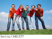 Купить «Молодые люди на траве показывают пальцем в камеру», фото № 340577, снято 16 декабря 2018 г. (c) Losevsky Pavel / Фотобанк Лори
