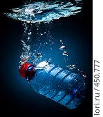 Купить «Бутылка с питьевой водой, падающая в воду, на черно-синем фоне с воздушными пузырьками», фото № 450777, снято 9 июля 2008 г. (c) Мельников Дмитрий / Фотобанк Лори