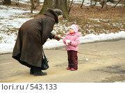 Маленькая девочка со снежком разговаривает с бабушкой. Стоковое фото, фотограф Losevsky Pavel / Фотобанк Лори
