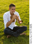 Музыкант играет на дудке сидя на траве. Стоковое фото, фотограф Елена Куколева / Фотобанк Лори
