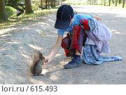 Девочка кормит белку (2008 год). Редакционное фото, фотограф A Большаков / Фотобанк Лори