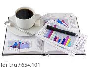 Бизнес-ежедневник со стоящей на нем чашкой кофе и экономическими цветными графиками на странице. Изолирован от фона. Стоковое фото, фотограф Vitas / Фотобанк Лори