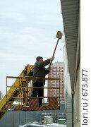 Рабочий сбивает сосульки с крыши (2009 год). Редакционное фото, фотограф Борис Двойников / Фотобанк Лори