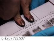 Купить «Клиент милиции прижимает большие пальцы к специальной таблице», фото № 728537, снято 20 января 2009 г. (c) Максим Попурий / Фотобанк Лори