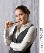 Задумчивая улыбающаяся девушка с ручкой в зубах. Стоковое фото, фотограф Смирнов Владимир / Фотобанк Лори