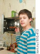 Купить «Юноша собирается разогреть еду в микроволновке», фото № 810413, снято 28 марта 2009 г. (c) Ирина Солошенко / Фотобанк Лори