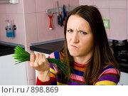 Купить «Недовольная девушка держит в руке пучок лука», фото № 898869, снято 24 мая 2009 г. (c) Сергей Новиков / Фотобанк Лори