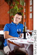Купить «Молодой человек  сидит за столом в ресторане и смотрит на бокал красного вина», фото № 948549, снято 25 июня 2009 г. (c) Баевский Дмитрий / Фотобанк Лори