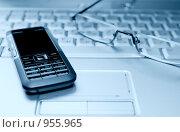 Купить «Мобильный телефон и очки на клавиатуре ноутбука. Тонированное изображение», фото № 955965, снято 29 июля 2008 г. (c) Сергей Плахотин / Фотобанк Лори