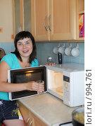 Купить «Девушка ставит стакан воды в микроволновку», фото № 994761, снято 24 июля 2009 г. (c) Гладских Татьяна / Фотобанк Лори
