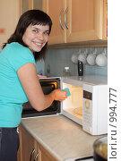 Купить «Девушка моет микроволновую печь», фото № 994777, снято 24 июля 2009 г. (c) Гладских Татьяна / Фотобанк Лори
