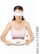Купить «Девушка с завязанными глазами сидит перед тарелкой с красным крестом», фото № 1113045, снято 12 сентября 2009 г. (c) Raev Denis / Фотобанк Лори