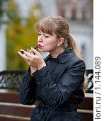Купить «Девушка красит губы на скамейке в парке», фото № 1144089, снято 10 октября 2009 г. (c) Сергей Шумаков / Фотобанк Лори