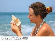 Купить «Красивая женщина с ракушкой в руках на берегу моря», фото № 1229409, снято 13 июля 2009 г. (c) Losevsky Pavel / Фотобанк Лори