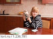 Купить «Девушка на кухне решает, куда потратить деньги», эксклюзивное фото № 1236781, снято 23 ноября 2009 г. (c) Ольга Хорькова / Фотобанк Лори