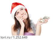 Купить «Задумчивая девушка с деньгами в колпаке Санта-Клауса», фото № 1252649, снято 28 ноября 2009 г. (c) Ирина Золина / Фотобанк Лори