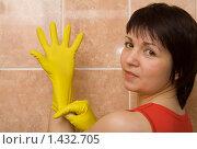 Молодая женщина надевает хозяйственные перчатки. Стоковое фото, фотограф Kribli-Krabli / Фотобанк Лори