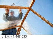 Купить «Плотник обтягивает пленкой каркас теплицы», фото № 1448053, снято 12 апреля 2009 г. (c) Александр Паррус / Фотобанк Лори