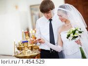Купить «Новобрачные зажигают свечи в церкви», фото № 1454529, снято 13 июня 2009 г. (c) Владимир Сурков / Фотобанк Лори