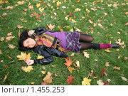 Купить «Радостная девушка лежит на ковре из осенних листьев», фото № 1455253, снято 8 октября 2009 г. (c) Зореслава / Фотобанк Лори