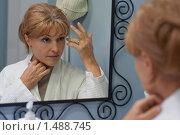 Купить «Женщина средних лет смотрит в зеркало», фото № 1488745, снято 15 ноября 2009 г. (c) Иван Бондаренко / Фотобанк Лори