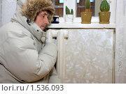 Мужчина в теплой куртке в холодной комнате греется возле батареи. Стоковое фото, фотограф Левончук Юрий / Фотобанк Лори