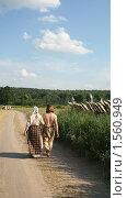 Пара в деревенской одежде идет вдоль частокола. Стоковое фото, фотограф Галина Гаврилова / Фотобанк Лори