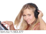 Купить «Крупный портрет молодой симпатичной девушки с наушниками, играющей на миди-клавиатуре», фото № 1563377, снято 28 декабря 2009 г. (c) Александр Егорин / Фотобанк Лори