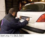 Мужчина прикрепляет к автомобилю рамку для государственного регистрационного знака (2010 год). Редакционное фото, фотограф Ольга Спиркина / Фотобанк Лори