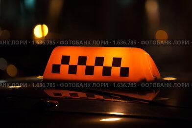 Знак такси на крыше автомобиля - черные шашечки на желтом фоне среди огней ночного города