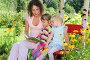 Мама с дочками читают книгу в летнем саду, фото № 1642869, снято 2 августа 2009 г. (c) Losevsky Pavel / Фотобанк Лори