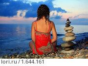 Купить «Красивая женщина в красном сарафане сидит рядом с пирамидой из гальки», фото № 1644161, снято 9 июля 2009 г. (c) Losevsky Pavel / Фотобанк Лори
