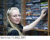 Купить «Девушка в магазине выбирает диск», фото № 1662381, снято 20 апреля 2010 г. (c) Яков Филимонов / Фотобанк Лори