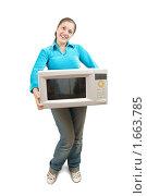 Купить «Девушка держит в руках микроволновою печь», фото № 1663785, снято 10 октября 2009 г. (c) Яков Филимонов / Фотобанк Лори