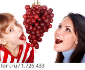 Купить «Счастливые мама с дочкой едят виноград», фото № 1726433, снято 6 декабря 2009 г. (c) Gennadiy Poznyakov / Фотобанк Лори