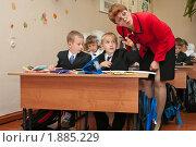 Купить «Учительница помогает первоклассникам на уроке», фото № 1885229, снято 1 сентября 2009 г. (c) Кекяляйнен Андрей / Фотобанк Лори